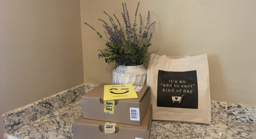 Boxes with Anniversary Sale stickers, add to cart kind of day canvas bag, vase with lavender