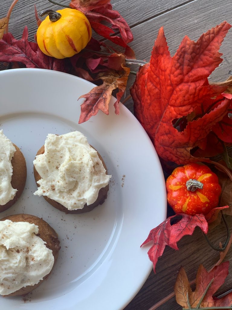 Pumpkin Cookies with Cream Cheese Frosting on White Plate with Leaves and Pumpkins