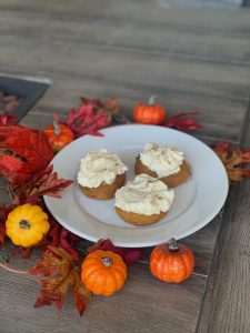 Pumpking Cookies with Cream Cheese Frosting on White Plate with leaves and small pumpkins