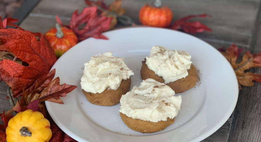 3 Pumpkin Cookies with cream cheese frosting on white plate surrounded by pumpkin and fall leaf decor on table